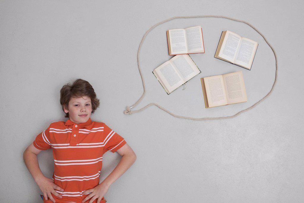 Boy with books in speech bubble, portrait : Stock Photo
