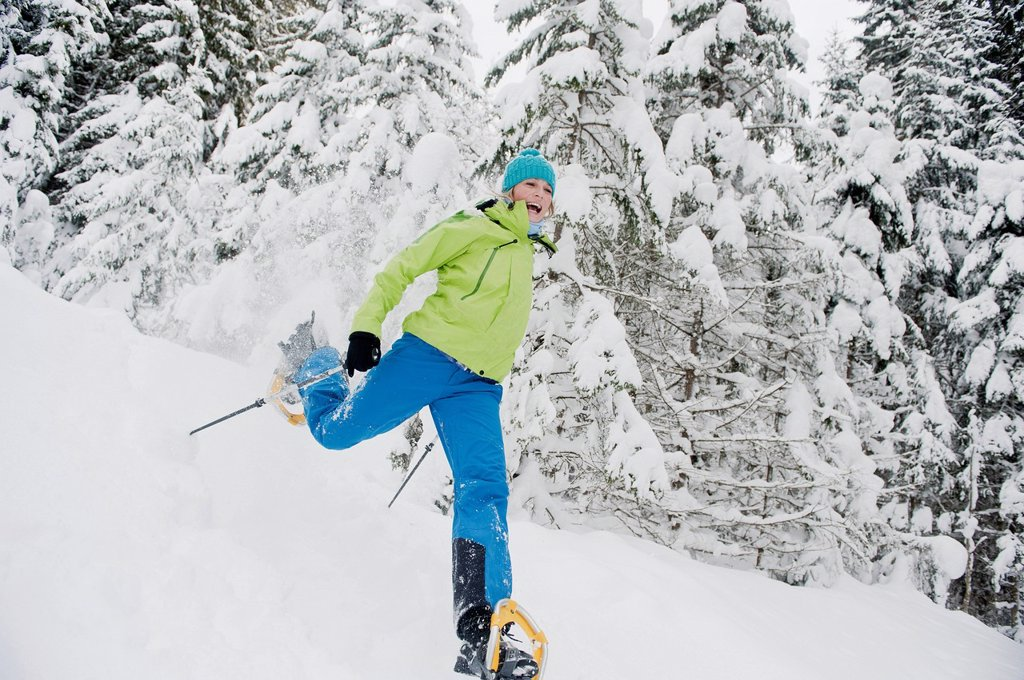 Austria, Salzburg County, Young woman snowshoeing : Stock Photo