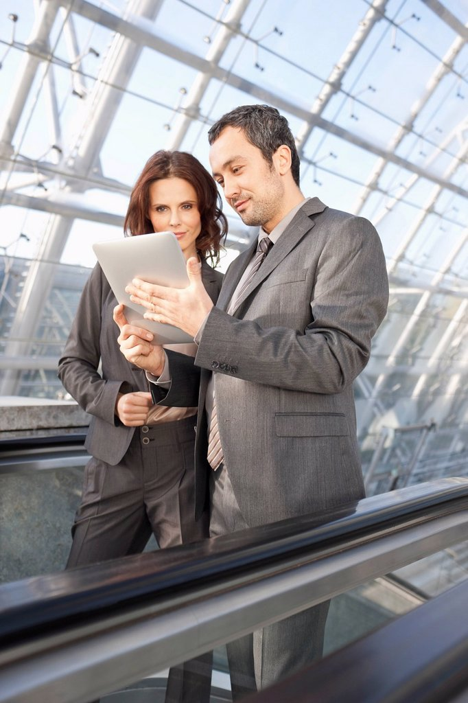 Germany, Leipzig, Business people using digital tablet on escalator : Stock Photo