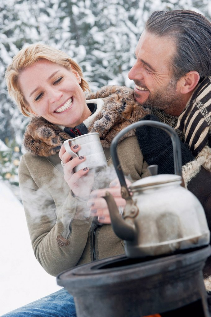 Stock Photo: 1815R-105146 Austria, Salzburg County, Couple sitting near camping stove, smiling