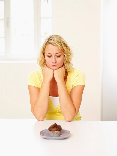 Stock Photo: 1815R-105856 Mid adult woman looking at muffin