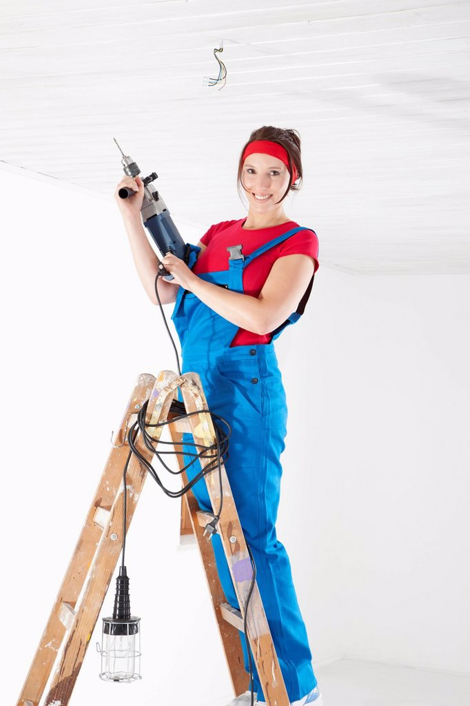 Germany, Bavaria, Young woman drilling with electric drill : Stock Photo