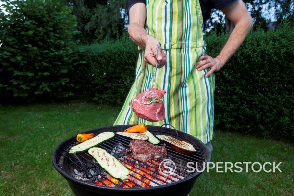 Germany, Mature man holding meat over barbecue grill : Stock Photo