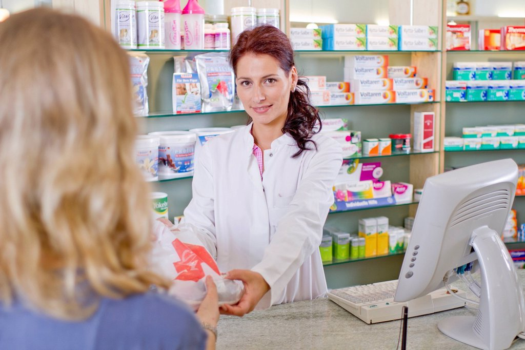 Germany, Brandenburg, Pharmacist handing medicne to woman : Stock Photo