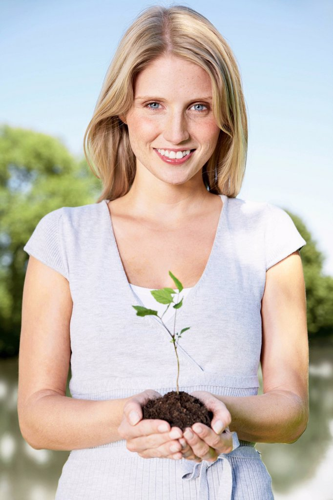 Germany, Cologne, Young woman holding seedling, smiling, portrait : Stock Photo