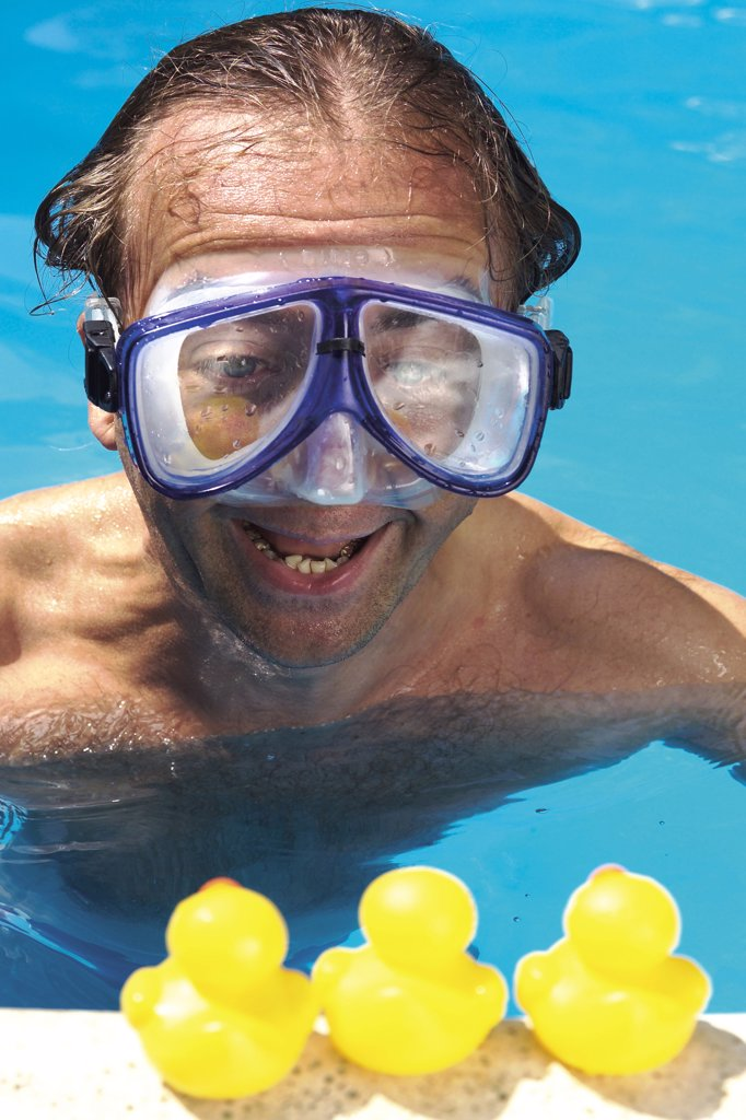 Man in swimming pool looking at plastic ducks : Stock Photo