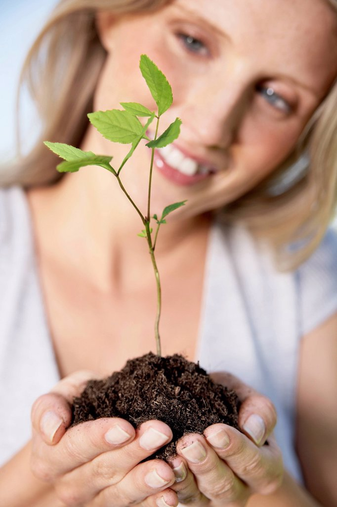 Germany, Cologne, Young woman holding seedling, smiling : Stock Photo