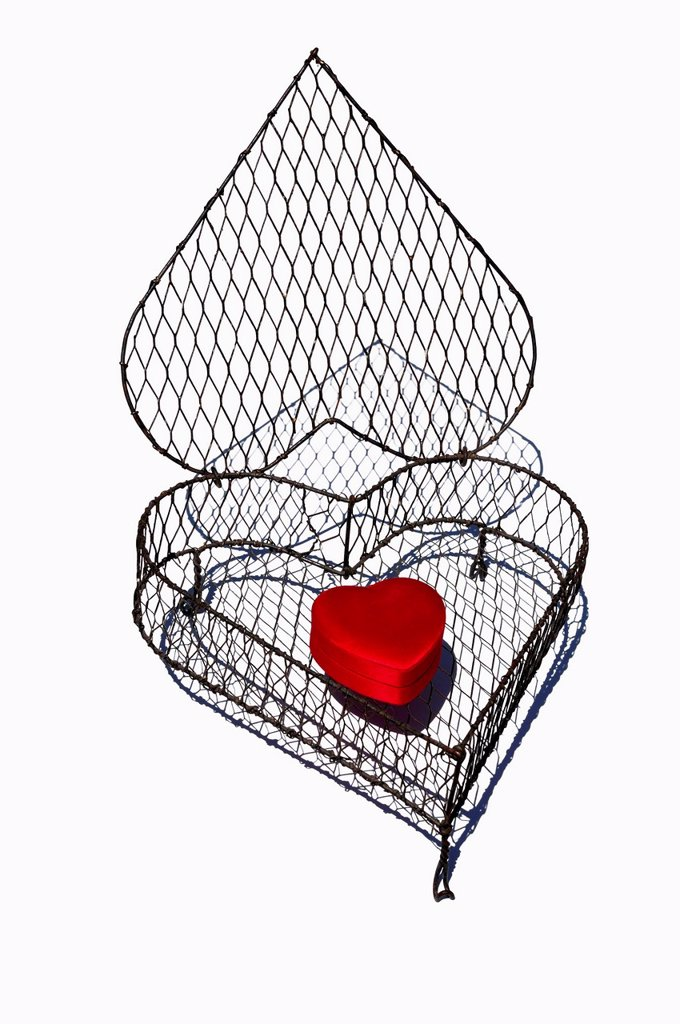 Stock Photo: 1815R-108597 Heart shape cage made by wire with red heart on white background, close up