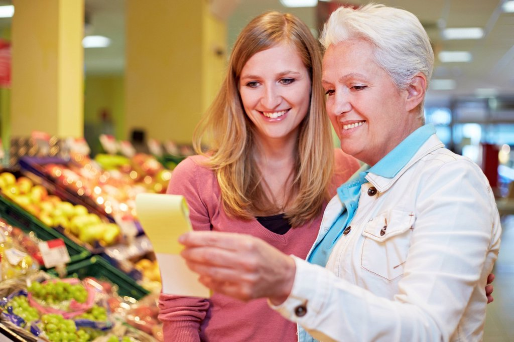 Germany, Cologne, Women with list in supermarket : Stock Photo