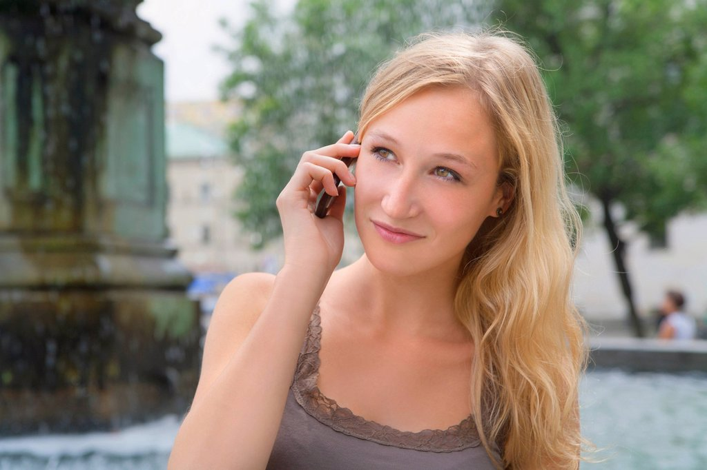 Stock Photo: 1815R-109224 Germany, Bavaria, Munich, Young woman talking on phone in front of Ludwig Maximilian University