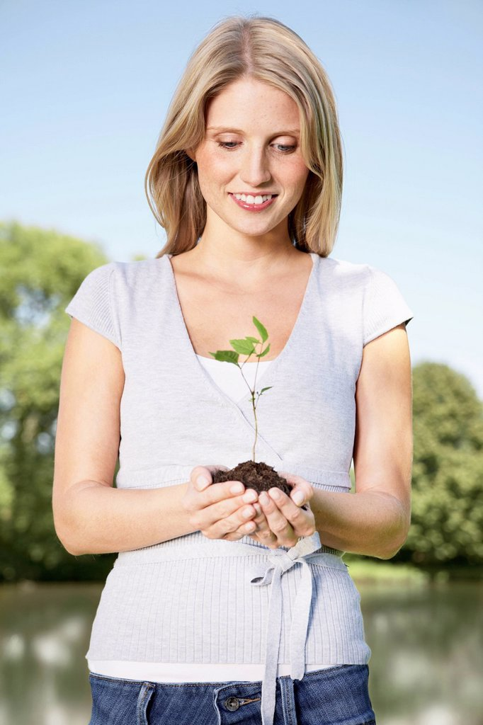 Stock Photo: 1815R-109376 Germany, Cologne, Young woman holding seedling, smiling
