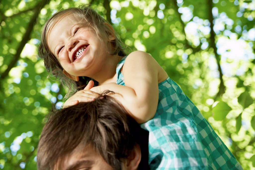 Germany, Cologne, Father carrying daughter on shoulders, smiling : Stock Photo