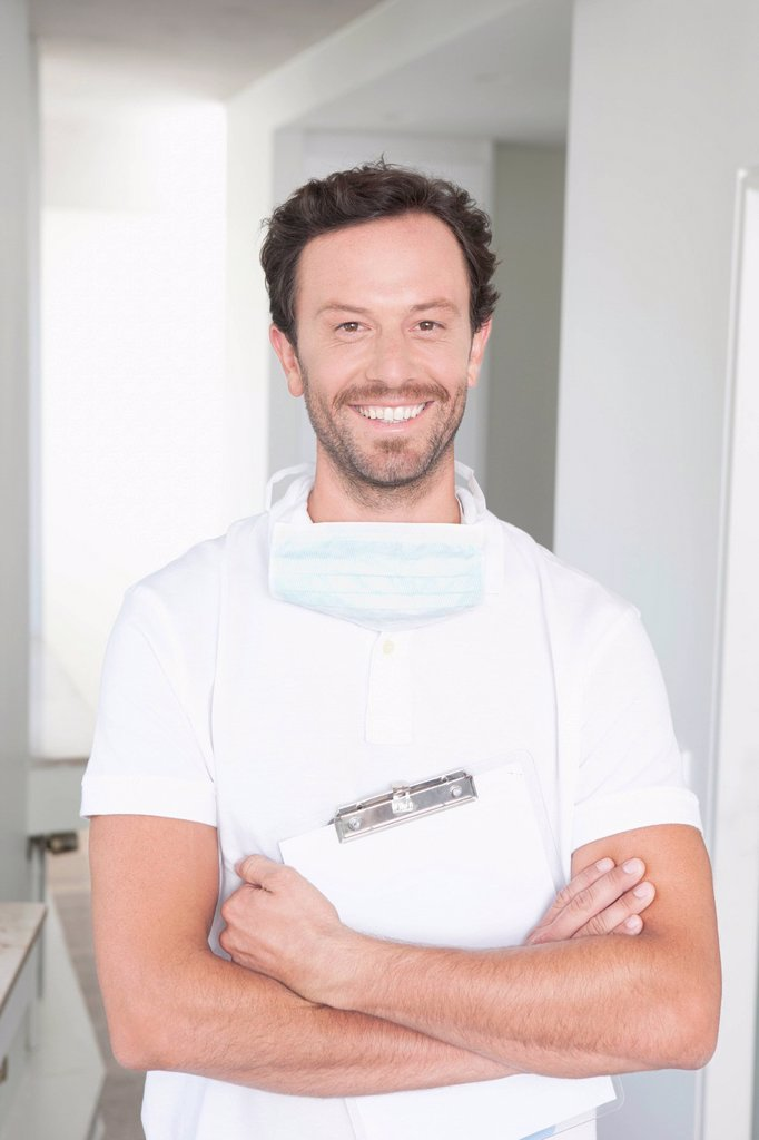 Stock Photo: 1815R-110626 Germany, Dentist holding clip board, smiling, portrait