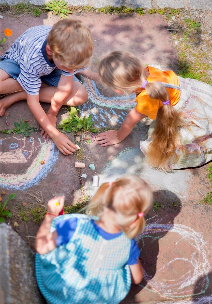 Germany, Bavaria, Group of children drawing on walkway with chalk : Stock Photo