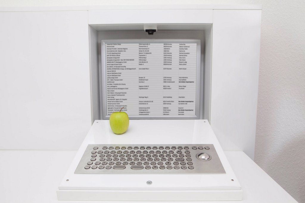 Germany, Apple on keyboard and screen installed in furniture : Stock Photo