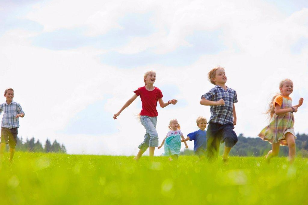 Germany, Bavaria, Group of children running through meadow : Stock Photo