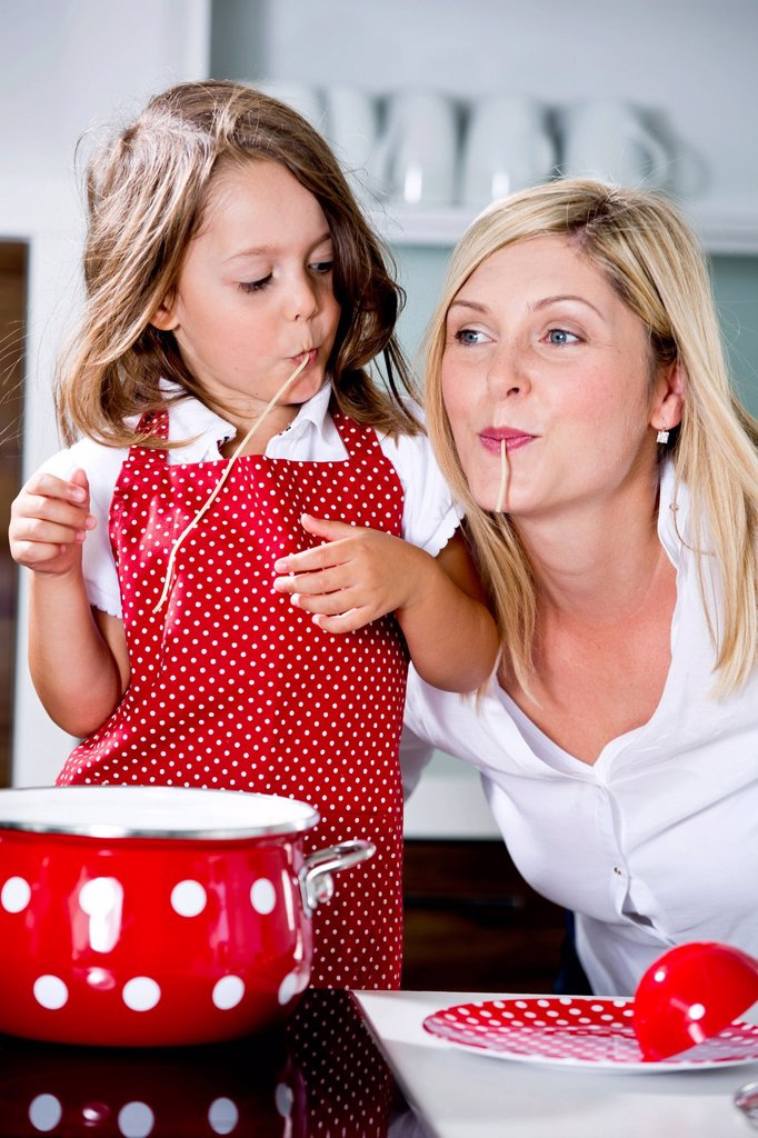Stock Photo: 1815R-111758 Germany, Mother and daughter eating noodles in kitchen