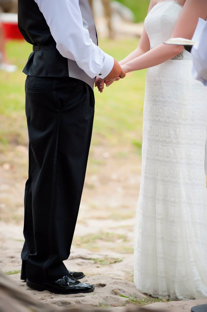 USA, Texas, Bride and groom holding hands, close up : Stock Photo