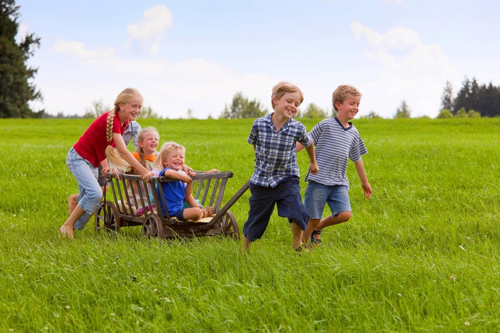 Germany, Bavaria, Group of children playing with hand cart : Stock Photo