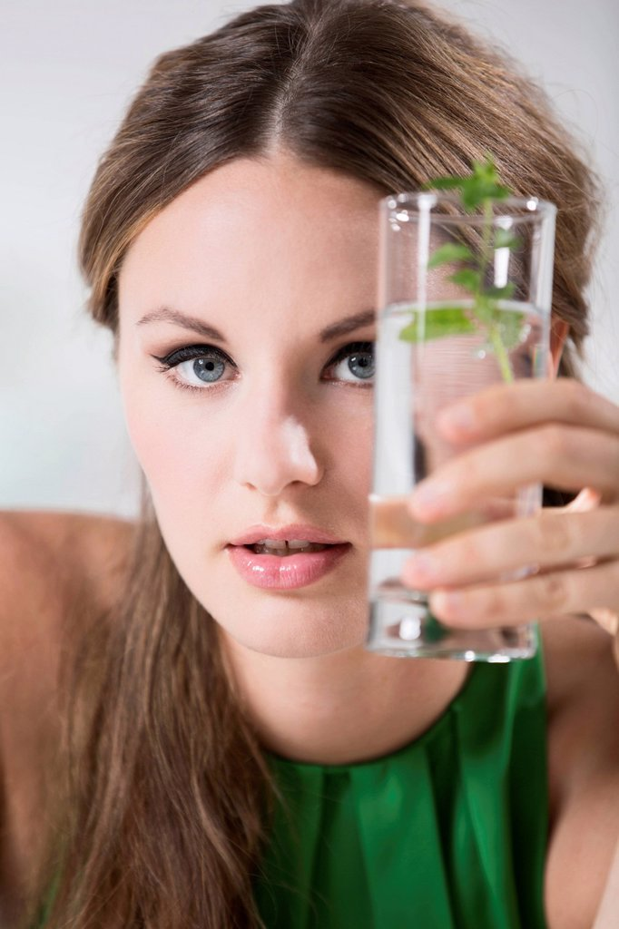 Germany, Young woman holding glass of water : Stock Photo