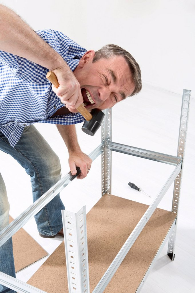 Stock Photo: 1815R-112891 Mature man building shelf