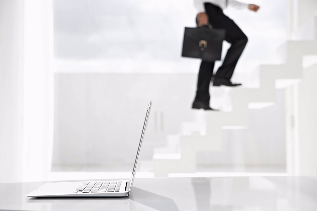 Spain, Businessman cimbing up stairs, laptop in foreground : Stock Photo
