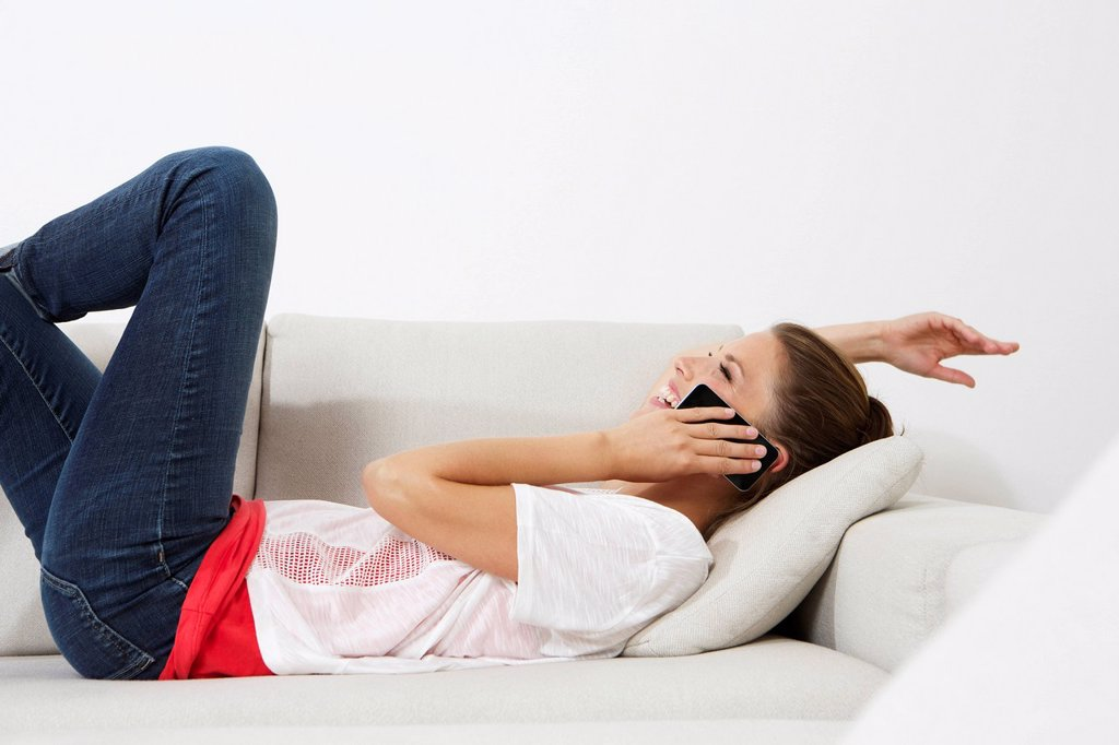 Stock Photo: 1815R-113063 Germany, Berlin, Young woman lying on couch and using smart phone