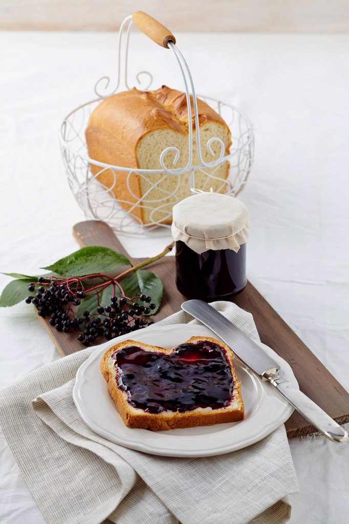 Stock Photo: 1815R-113332 Elderberry jam with white bread on wooden table
