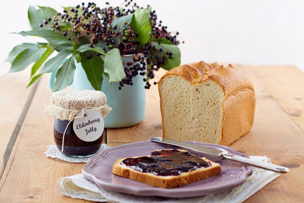 Stock Photo: 1815R-113333 Elderberry jam with white bread on wooden table