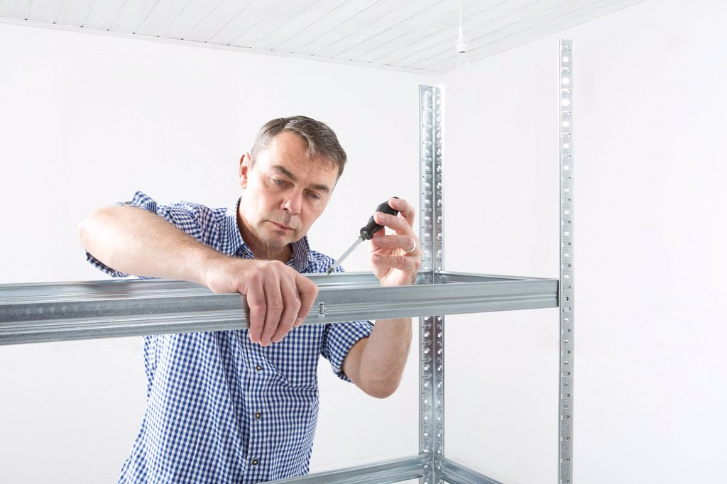Mature man building shelf : Stock Photo