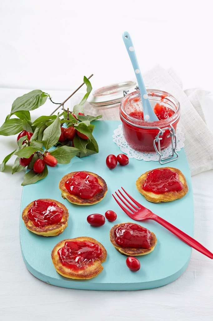 Cornel cherry jam with pancakes on chopping board : Stock Photo