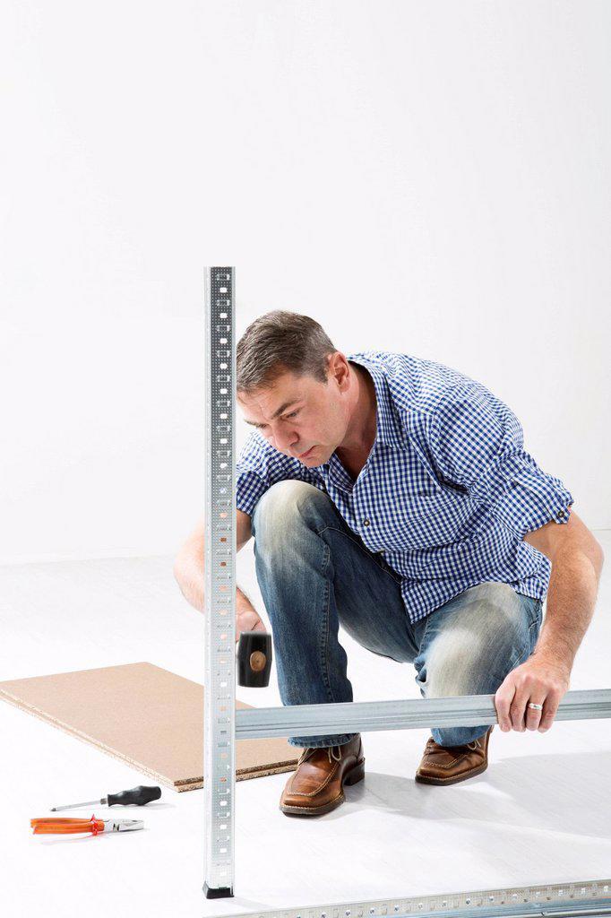 Mature man building shelf : Stock Photo