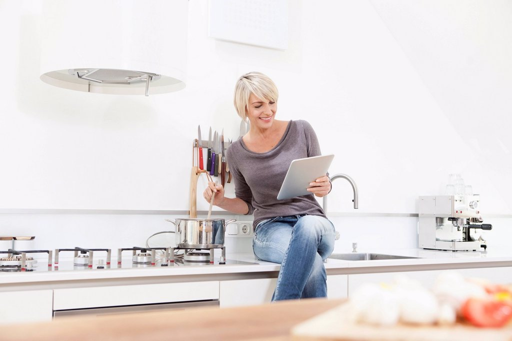 Stock Photo: 1815R-114496 Germany, Bavaria, Munich, Woman watching digital tablet and preparing food