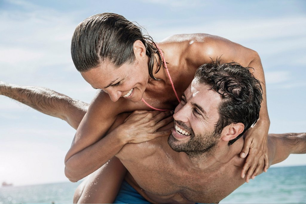 Spain, Mid adult man giving piggy back ride to woman : Stock Photo
