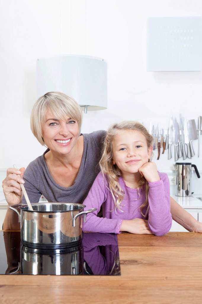 Stock Photo: 1815R-114732 Germany, Bavaria, Munich, Mother and daughter preparing food, smiling, portrait
