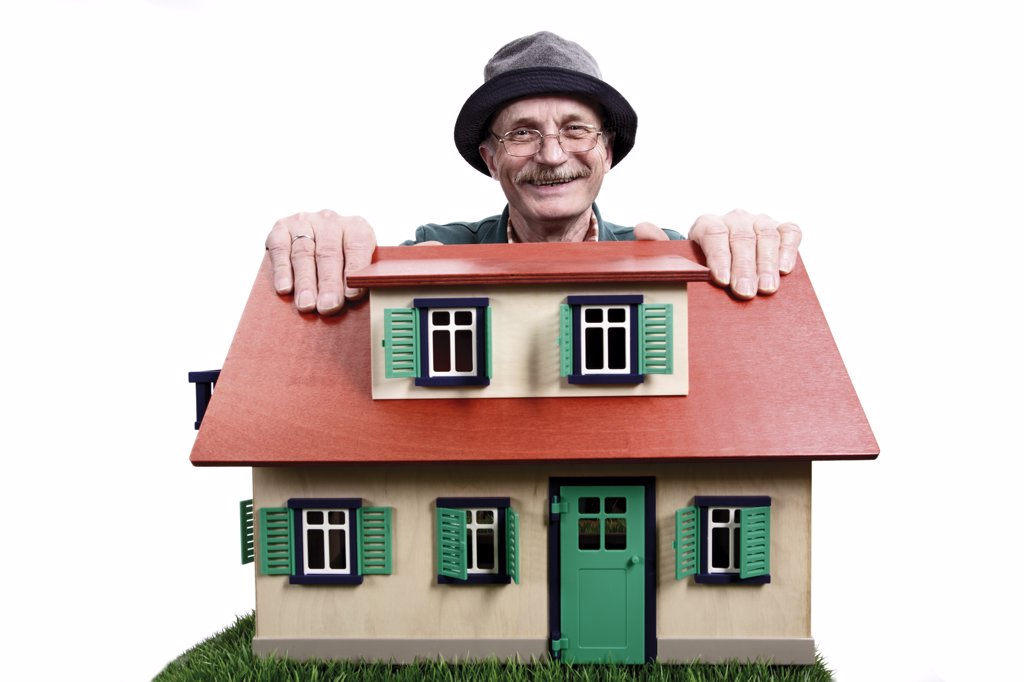 Old man with house, proud home owner : Stock Photo