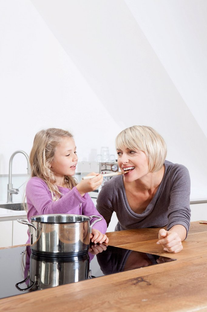 Stock Photo: 1815R-114986 Germany, Bavaria, Munich, Daughter feeding mother in kitchen, smiling