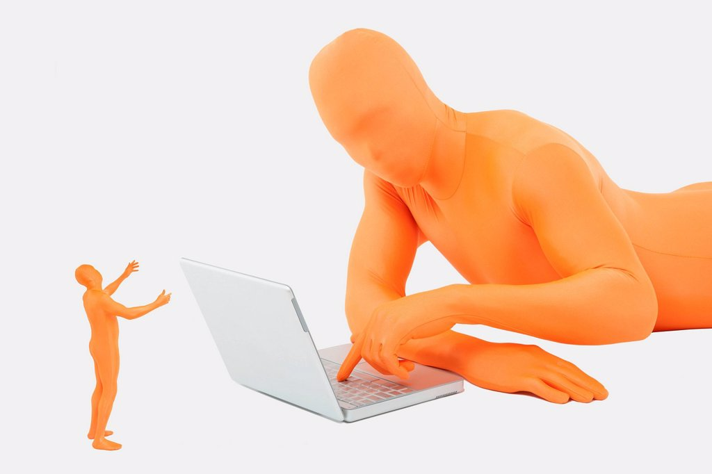 Men in orange zentai using laptop : Stock Photo