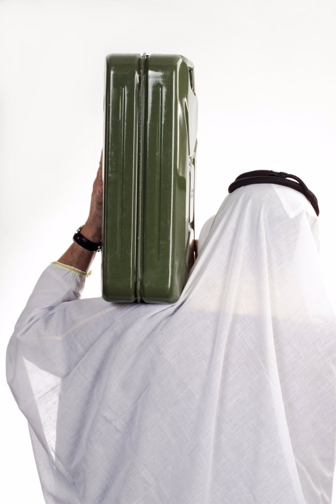 Man wearing traditional Arab dress, carrying petrol can on shoulder, rear view : Stock Photo
