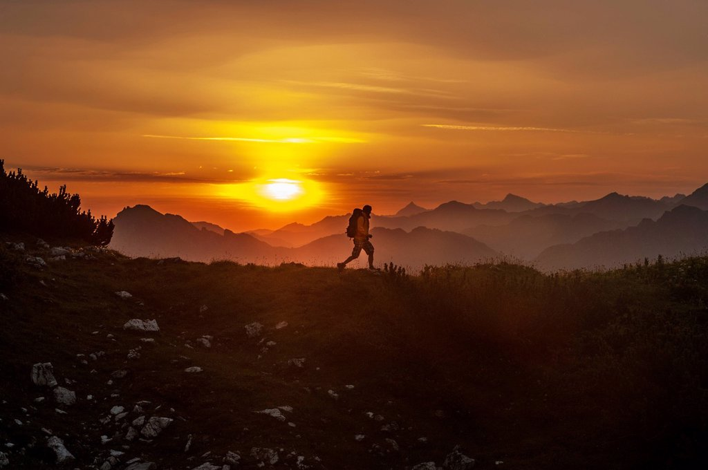 Stock Photo: 1815R-124627 Austria, Salzburg Country, Man hiking through Niedere Tauern mountains at sunrise