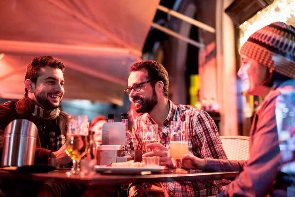 Stock Photo: 1815R-13029357 Three friends socialising at a pub at night