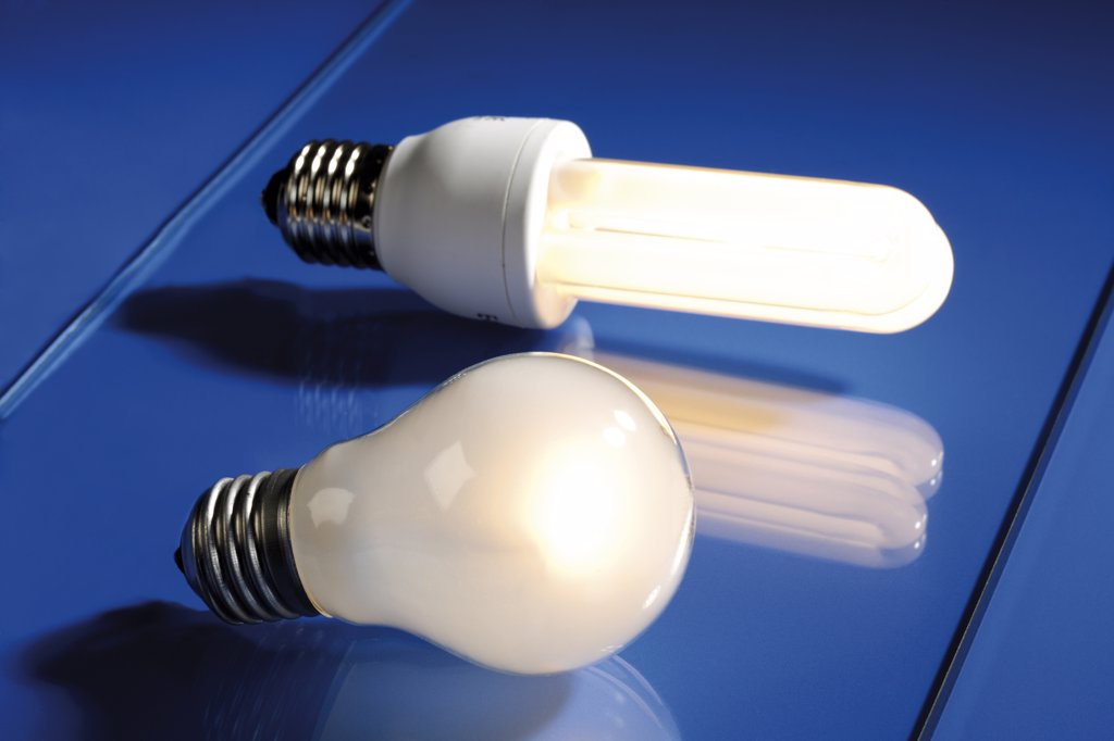 Energy saving lamp and electric bulb, close-up : Stock Photo
