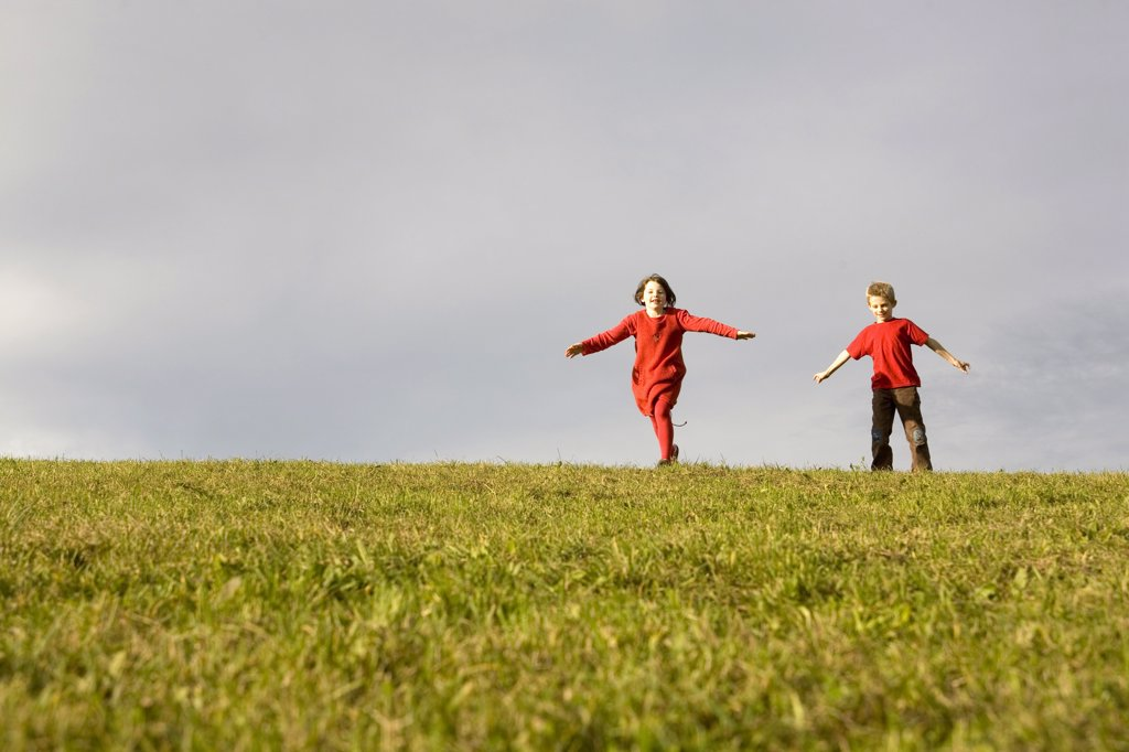 Stock Photo: 1815R-16886 Boy (10-12) and girl (7-9) running in meadow, arms outstretched