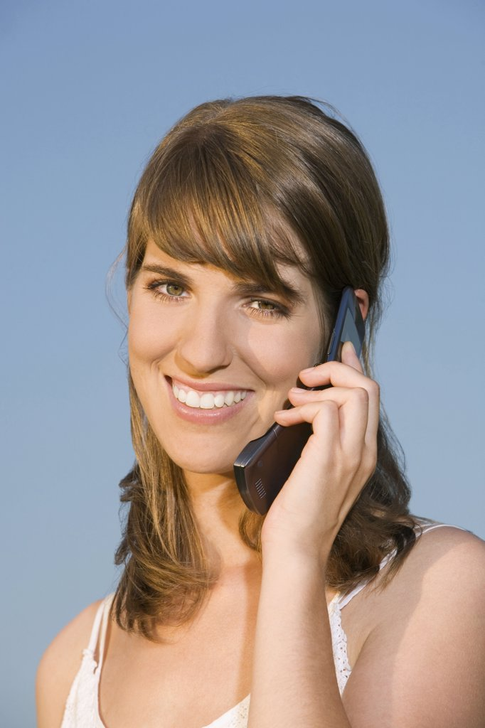 Stock Photo: 1815R-17063 Germany, Bavaria, Young woman using mobile phone, smiling, portrait
