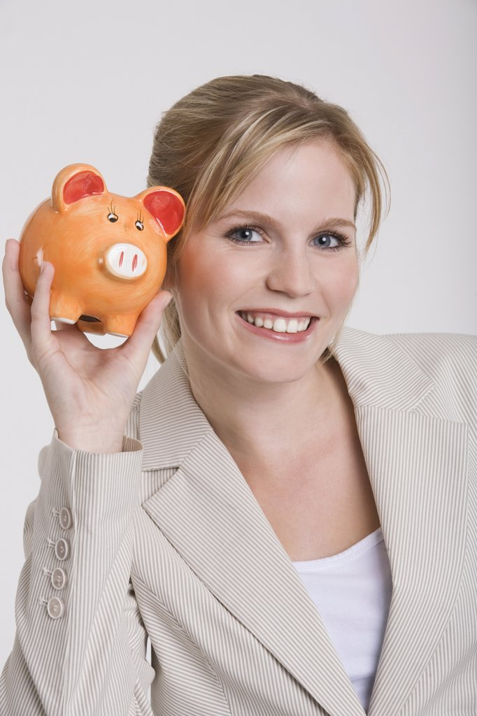 Stock Photo: 1815R-17325 Young woman holding a piggybank, portrait
