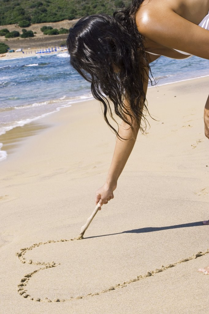 Woman drawing a heart into the sand : Stock Photo