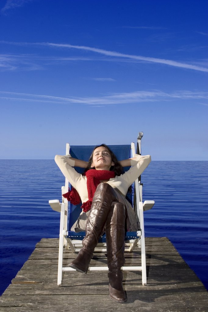 Stock Photo: 1815R-17712 Young woma sitting in dek chair on jetty, eyes closed
