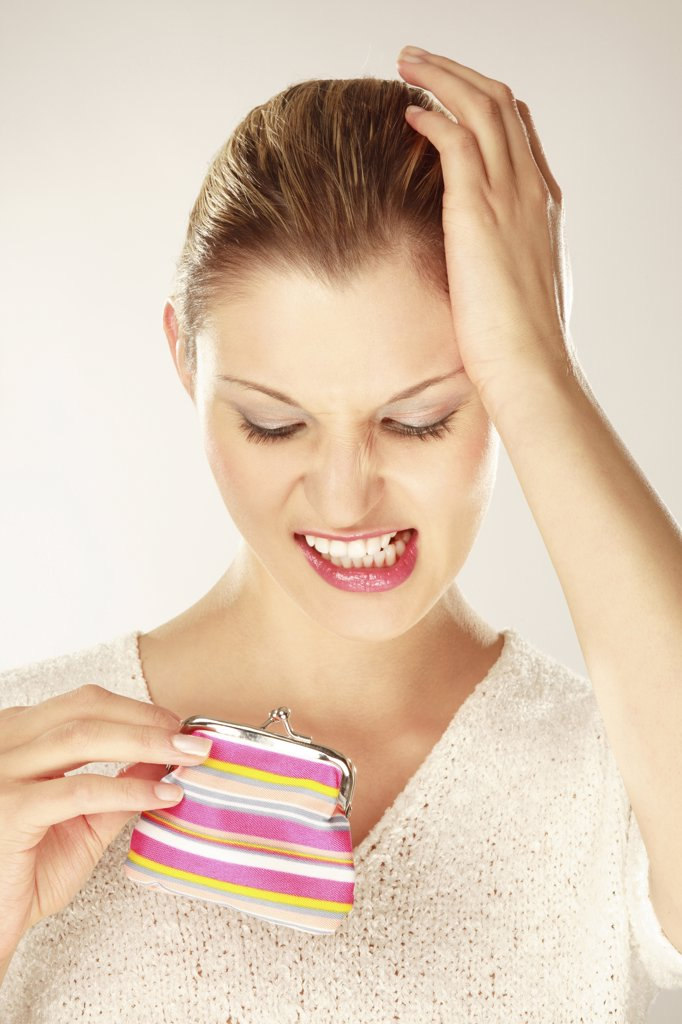 Young woman holding purse, clenching teeth, close-up : Stock Photo