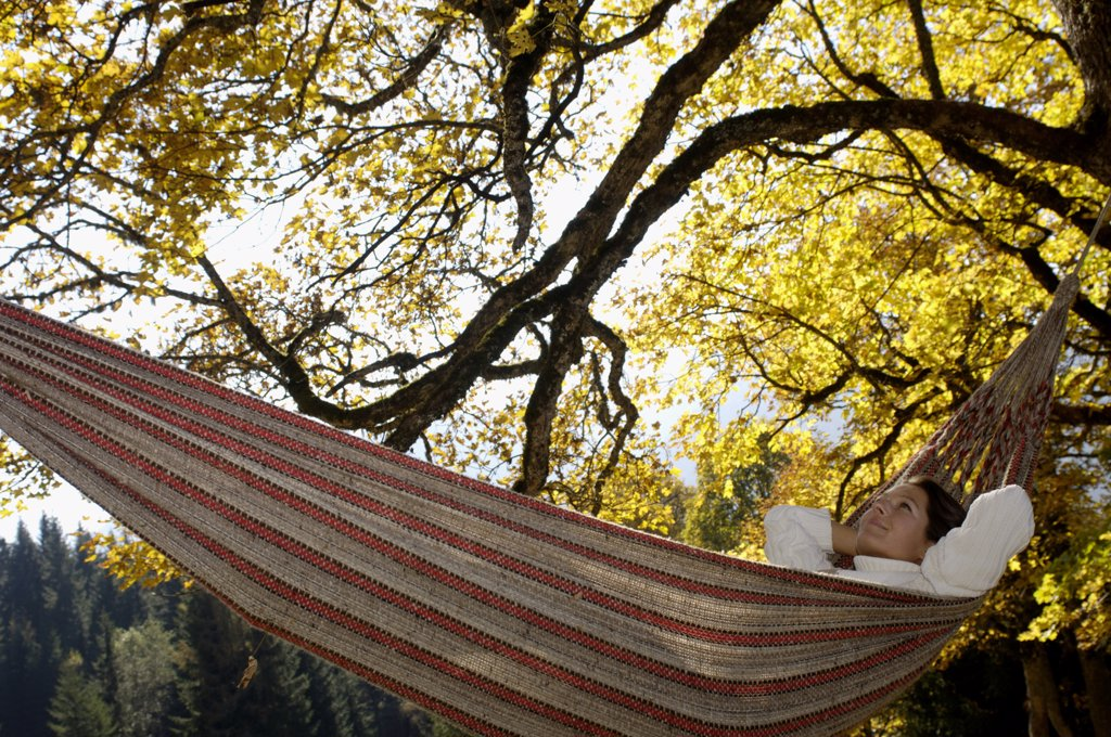 Stock Photo: 1815R-17973 Woman lying in hammock looking up