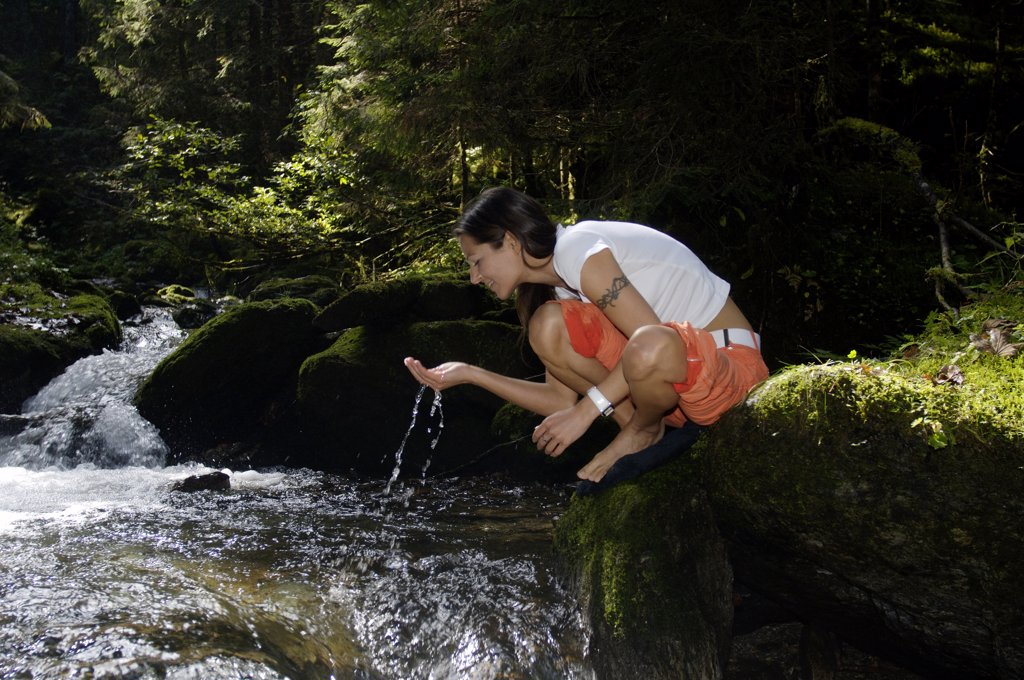 Austria, woman drinking water from stream in forest : Stock Photo